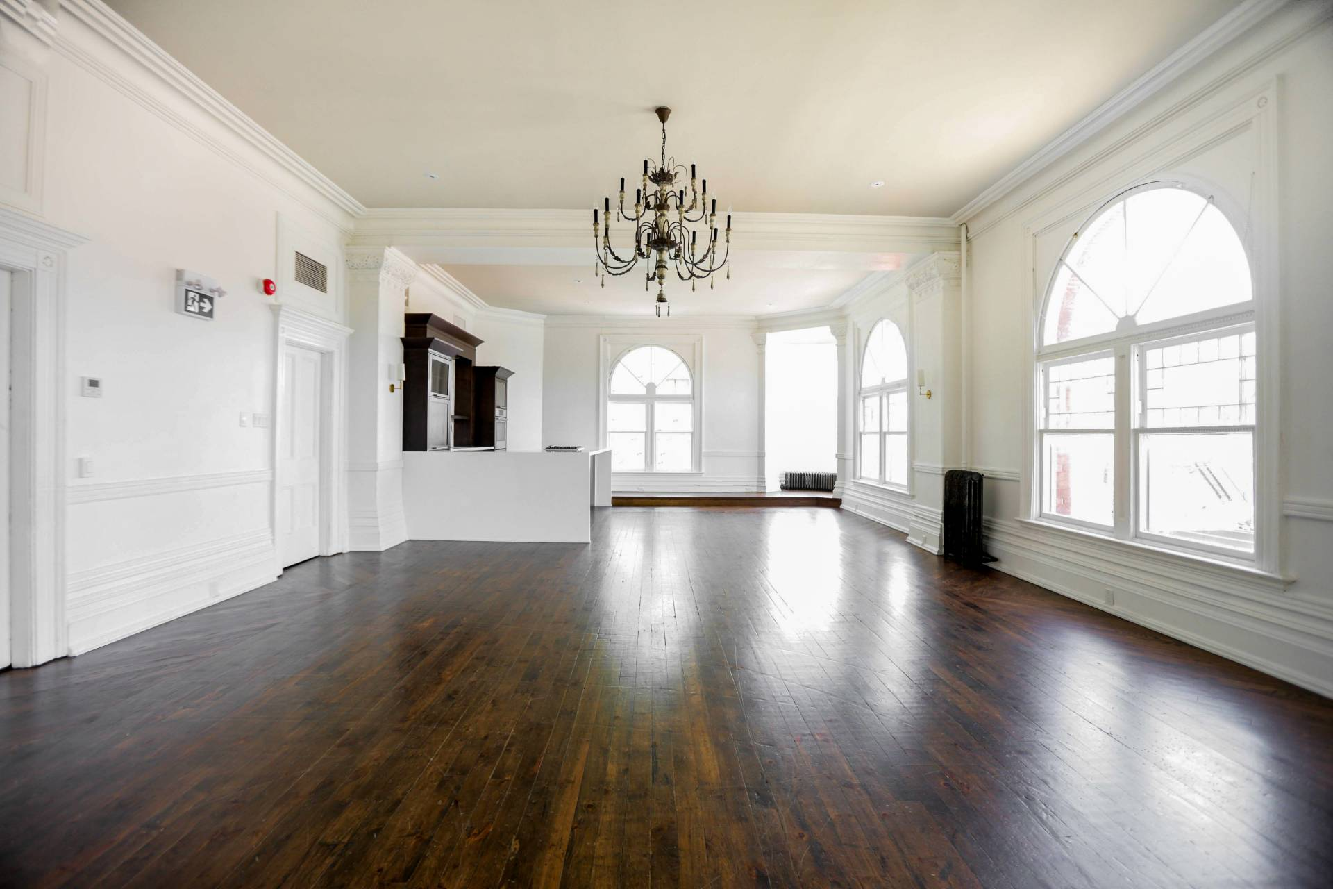 Dark Brown Hardwood Floor with Bright Walls and a chandelier