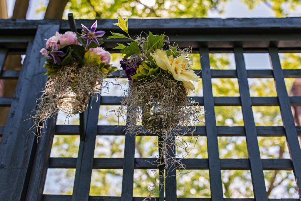 Two hanging floral arrangements with wood latices in the background
