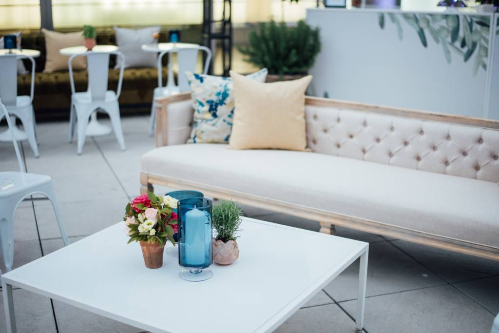 Photograph of event furniture rentals used at a garden wedding. there are metal tolix chairs in the background with small tables all white, a nice comfortable couch and coffee table with center piece in the front.