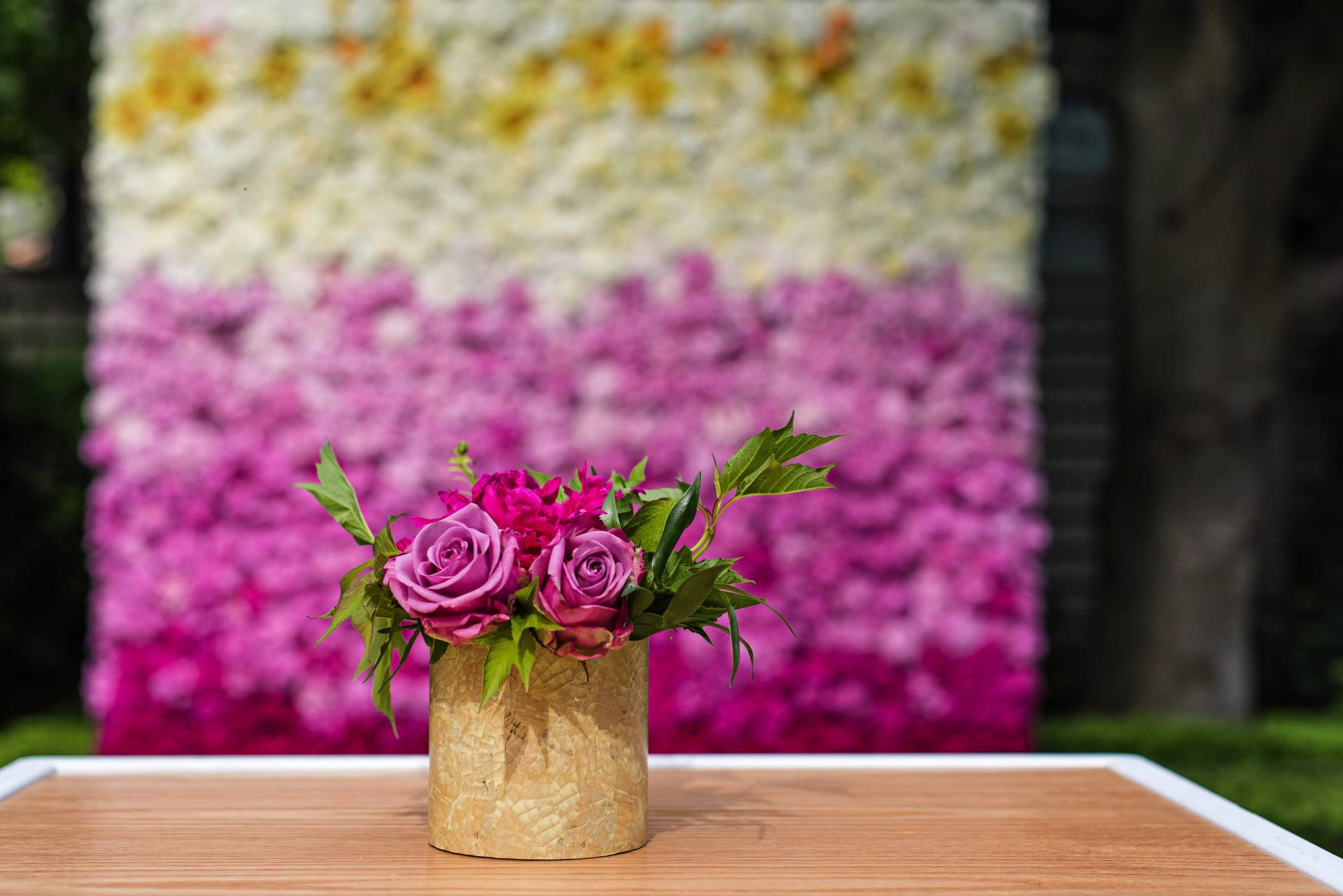 floral arrangement set on cruiser table with a multi-coloured flower wall faded in the background