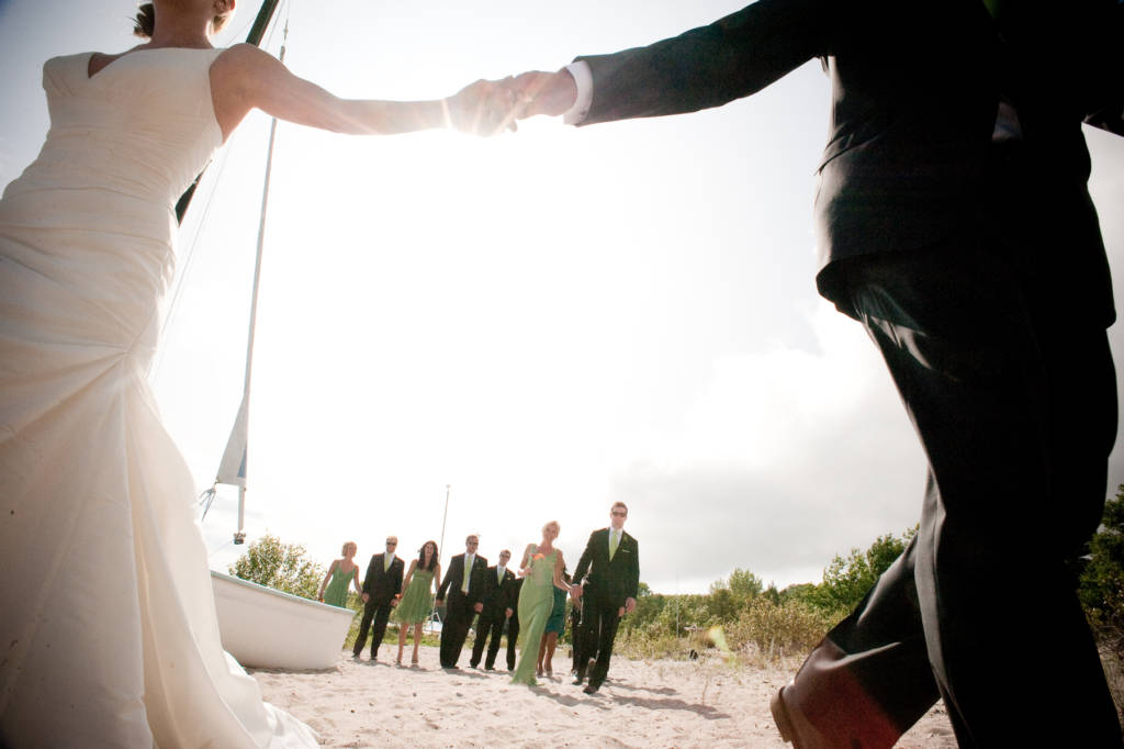 Newly weds holding hands on beach with the wedding party in the background