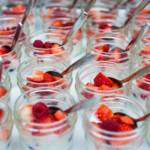 Image of Yogurt Cups served in a small glass jar with raspberries, blueberries and strawberries on top.