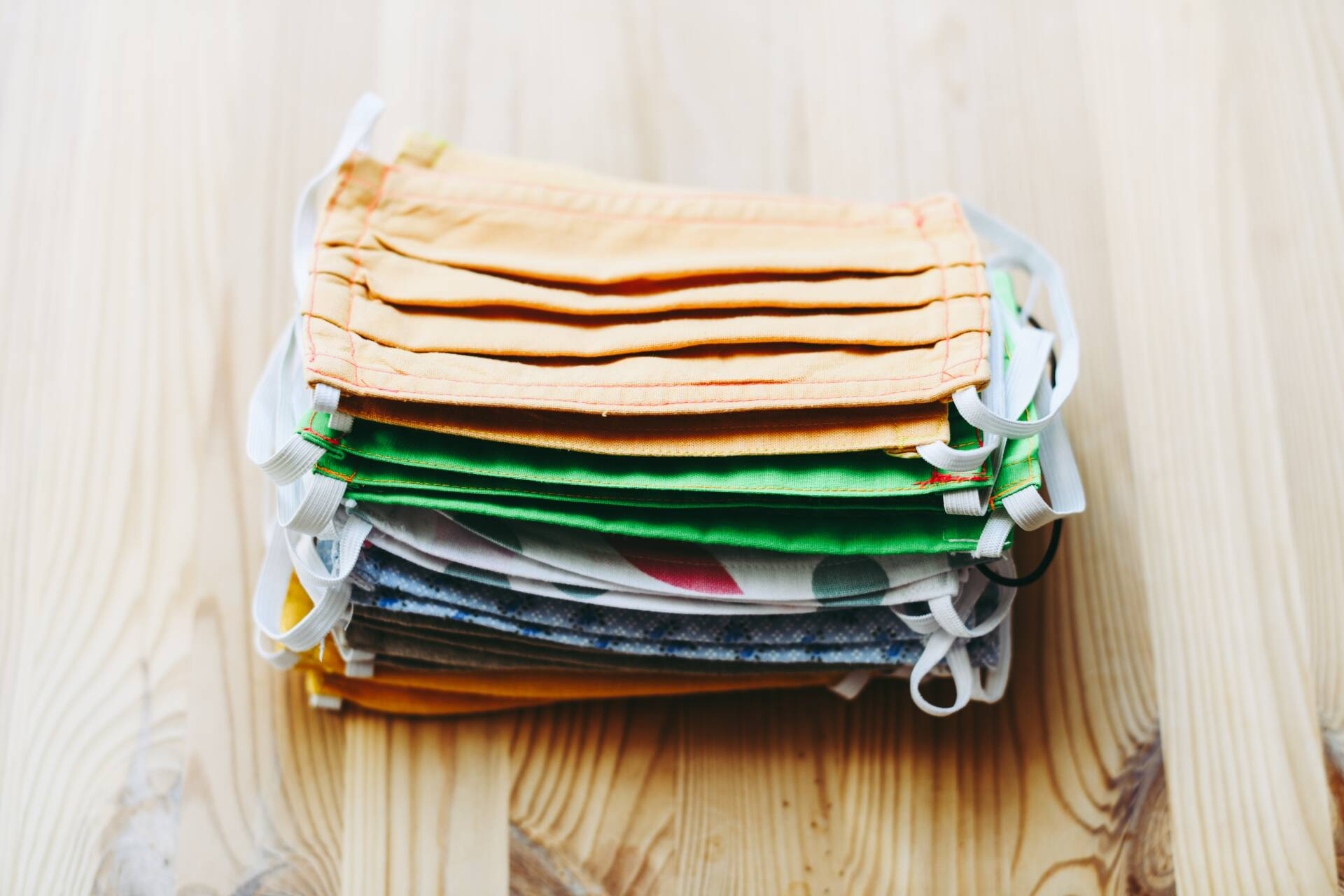 stack of cloth face masks on a wood table.